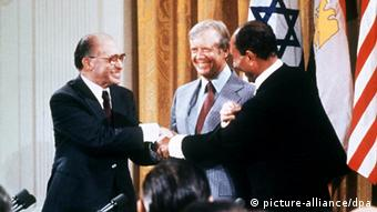Versöhnender Händedruck zwischen dem ägyptischen Präsidenten Anwar el Sadat (r) und dem israelischen Ministerpräsidenten Menachem Begin (l) am 17. September 1978 in Camp David (Maryland). In der Mitte US-Präsident Jimmy Carter