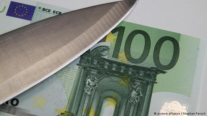 A big knife lies on a euro bank note to symbolize a debt cut