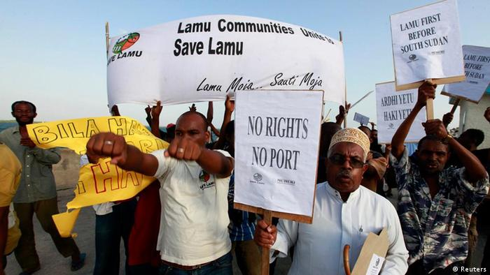 Protesters hold signs criticizing the Lamu coal project