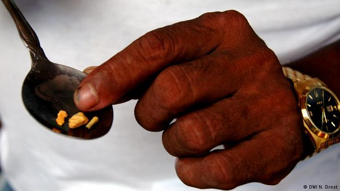 A man points to gold nuggets just melted down with a torch in the hamlet of Puerto Guamo