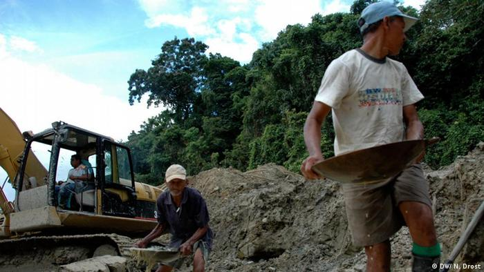 Gold panners work alongside excavators belonging to a rogue mining outfit, all of whom are after gold deposits in the remote Guamaco region of Colombia