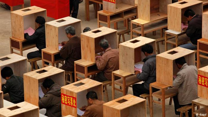Villagers write ballots at voting booths during an election to select village committees at a polling station set up outside a school in Wukan village, Lufeng city, south China's Guangdong province, Saturday, March 3, 2012. The villagers in southeast China who ousted local leaders they accused of stealing their farmland have begun voting for new leadership in much-watched elections. (Foto:Vincent Yu/AP/dapd)