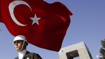 A Turkish soldier flanked by the Turkish flag (AP Photo/Murad Sezer)