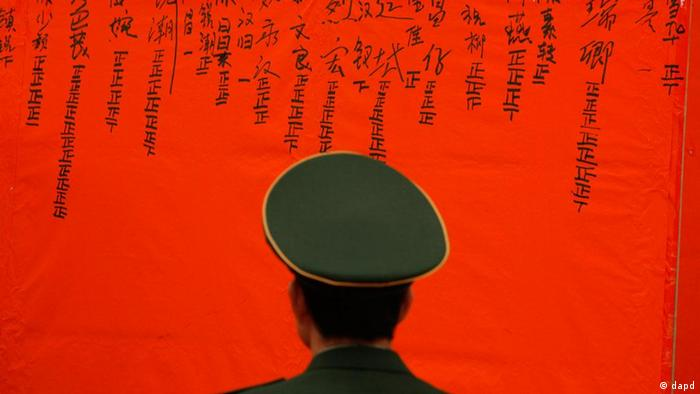 A Chinese police officer guards in front of a board to show result of counting votes for the candidates during an election to select village committees at a polling station in Wukan village, Lufeng city, south China's Guangdong province, Saturday, March 3, 2012. Villagers who rebelled against officials they accused of stealing their farmland voted for new leaders on Saturday in a much-watched election reformers hope will promote democracy as a way to settle many of the myriad disputes besetting China. (Foto:Vincent Yu/AP/dapd)