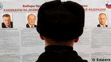 A Russian navy looks at the list of presidential candidates at a polling station in St.Petersburg, March 4, 2012. Vladimir Putin is almost certain to win a third presidential term in an election that began on Sunday in Russia's far east, though opponents have challenged the legitimacy of a vote they say is skewed in his favour. Reuters/Alexander Demianchuk (RUSSIA - Tags: POLITICS ELECTIONS)