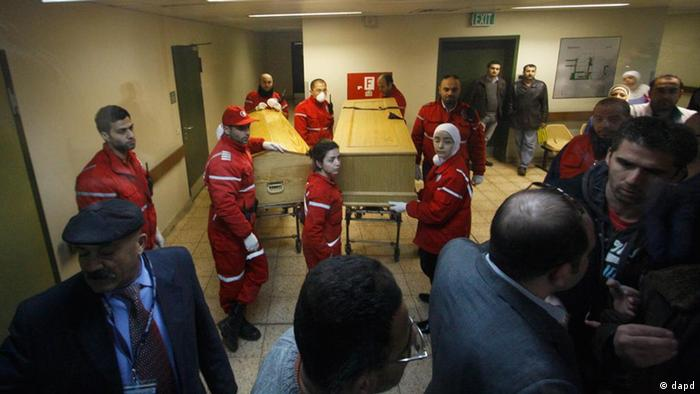 Syrian Red Crescent workers stand with the coffins of American journalist Marie Colvin, left, and French photojournalist Remi Ochlik at Assad hospital in Damascus, Syria