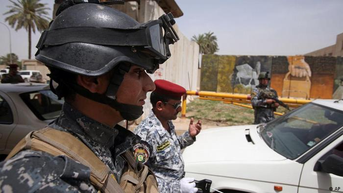 Iraqi police search cars at a checkpoint in central Baghdad, Iraq.