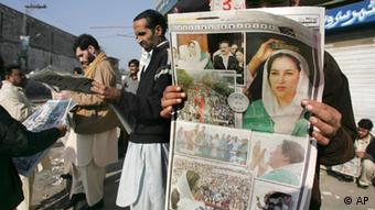 People read the morning newspapers with headline story of Pakistan's former Prime Minister Benazir Bhutto's assassination, at a newspapers stall in Rawalpindi, Pakistan on Friday, Dec. 28, 2007. (AP Photo/Anjum Naveed)
