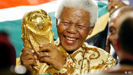 Former South African President Nelson Mandela lifts the World Cup trophy after the FIFA's executive committee announced that South Africa will host the 2010 FIFA World Cup, in Zurich, Switzerland, Saturday, May 15, 2004. FIFA's executive committee on Saturday picked South Africa ahead of Morocco and Egypt for the first World Cup to be staged in Africa. (AP Photo/Michael Probst