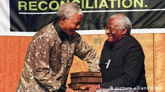 South African President Nelson Mandela (L) receives a five volumes of Truth and Reconciliation Commission final report from Archbishop Desmond Tutu, in Pretoria 29 October. The report reveals human rights abuse by various political parties during the Nationalist Party (NP) rule. Accepting the report, Mandela acknowledged that the wounds of the period of repression and resistance were too deep to have been healed by the TRC alone. dpa