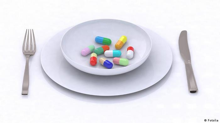 Symbolic serving of a bowl filled with pills and tablets inbetween a knife and fork