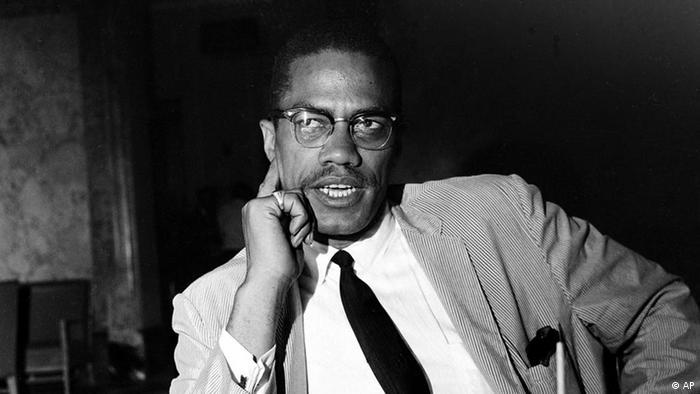 Malcolm X auf einem Foto von 1964. Er trägt Anzug und Krawatte und stützt seinen Kopf auf die Hand.