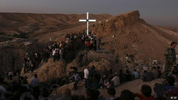 An illuminated cross is seen as Syrian Christians celebrate Holy Cross Day in Ma'loula, Syria on Sunday Sept. 13. 2009. Christians make up some 13 percent of Syria's 20 million population. (ddp images/AP Photo/Bassem Tellawi)