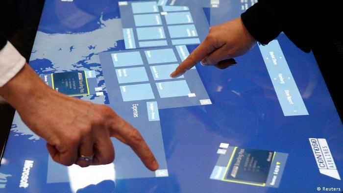 Staff members touch screens on cloud computing software to operate airlines, at the booth of Microsoft during preparations at the CeBit computer fair in Hanover, March, 5, 2012. The biggest fair of its kind open its doors to the public on March 6 and will run to March 10, 2012. REUTERS/Fabrizio Bensch (GERMANY - Tags: BUSINESS TELECOMS SCIENCE TECHNOLOGY)