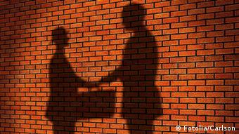 The shadows of two men shaking hands and exchanging a briefcase presumably full of cash contrast against a red brick wall (Photo: © Carlson)