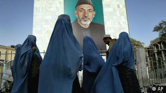 Burqa clad women walk along a shopping street in front of a giant portrait of Afghanistan President Hamid Karzai in Kabul