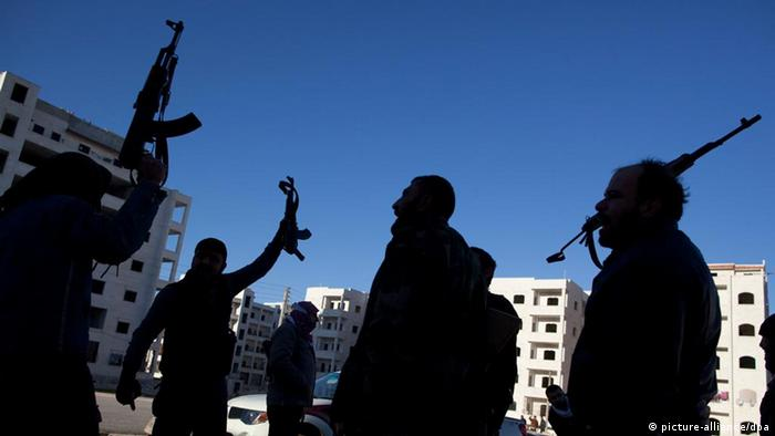 Free Syrian Army fighters chant anti-government slogans as they hold up their weapons near a building hit by a Syrian Army tank in Idlib, north Syria, Sunday, March 4, 2012. (Foto:Rodrigo Abd/AP/dapd)