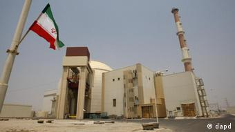 An Iranian flag flutters in front of the reactor building of the Bushehr nuclear power plant