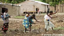 Frauen, die auf einem Acker in Afrika arbeiten Frauen mit ihren Babys auf dem Rücken verrichten schwere Feldarbeit - eine alltägliche Szene im Dorf Caiense, das sich etwa eine Autostunde von der Provinzhauptstadt Huambo entfernt befindet (Foto vom 23.10.2006). Foto: Thomas Schulze +++(c) dpa - Report+++
