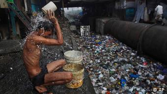 Man sitting at polluted canal, washing himself.