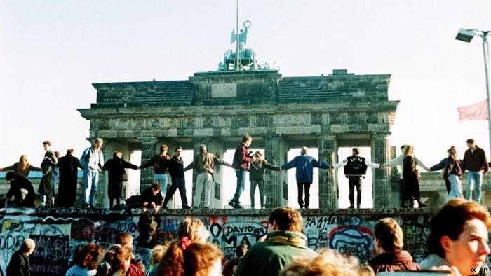 Berliners stand hand-in-hand on top of the Berlin Wall on November 10, 1989. The Brandenburg Gate looms in the background