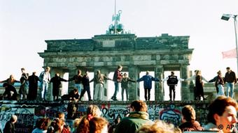 Dancing On The Wall - Berliners sing and dance atop the wall to celebrate the opening of East-West German borders November 10. Thousands of East German citizens moved into the West after East German authorities opened all border crossing points to the West. In background is the Brandenburg gate. (AP Photo/Thomas Kienzle/str) 10. November 1989