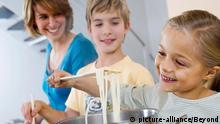 Mutter und Bruder sehen einem kleinen Mädchen bein Spaghettikochen zu