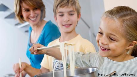 Mutter und Bruder sehen einem kleinen Mädchen bein Spaghettikochen zu (picture-alliance/Beyond)