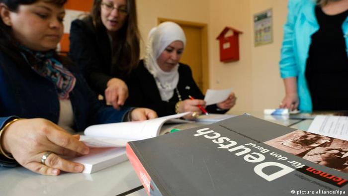 Eine Frau hilft jungen Frauen, im Vordergrund ein Buch mit dem Titel Deutsch lernen für den Beruf