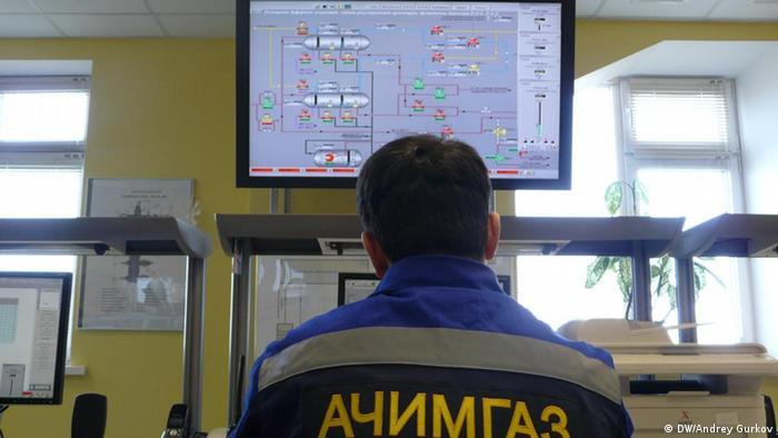 Оператор перед мониторами с надписью Ачимгаз следит за добычей газа
