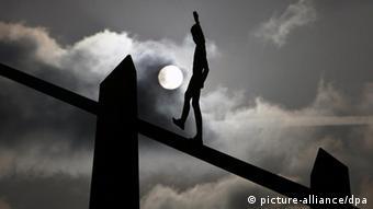 Ein balancierender Seiltänzer vor dem Nachthimmel