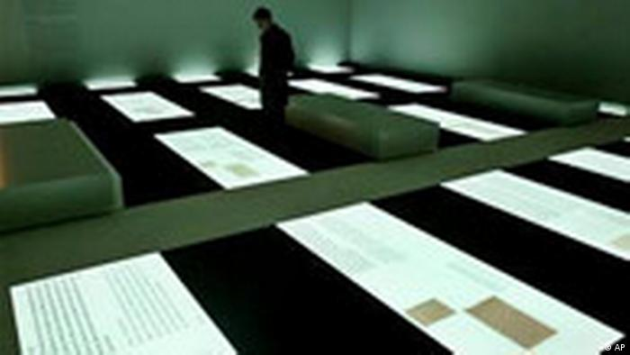An unidentified visitor looks at private documents of Holocaust victims inside the information center of the Holocaust memorial in Berlin Monday, May 9, 2005, one day before its opening ceremony. The memorial to the murdered Jews in Europe, created by U.S. architect Peter Eisenman, will open on May 10, 2005. (AP Photo/ Jan Bauer)