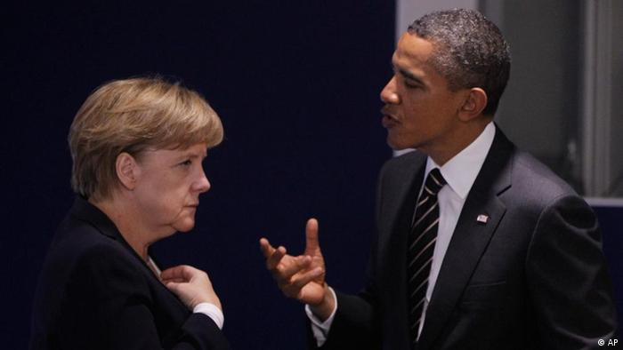 Wearing black business suits, German Chancellor Angela Merkel and US President Barack Obama speak to each other in a public setting.