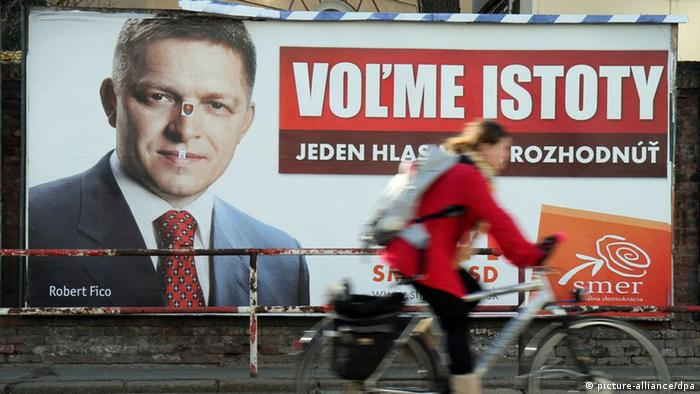 A cyclist passes by an election campaign poster showing the leader of the SMER Social Democracy party, Robert Fico, in Bratislava, Slovakia.