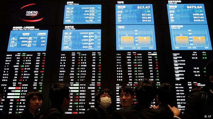 Junior high school students walk by an electronic stock board at the Tokyo Stock Exchange Photo:Itsuo Inouye/AP/dapd