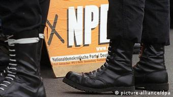 Jack boots in front of NPD sign Photo: Kalaene Jens dpa