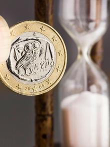 ARCHIV - Illustration - Eine griechische Euro-Münze neben einer Sanduhr, fotografiert in Frankfurt am Main am 20.05.2011. Griechenland kriegt seine Schulden nicht in den Griff, die Wirtschaft steckt tief in der Rezession und die Troika von EU, EZB und IWF stellt Athen in Sachen Sparprogramm ein schlechtes Zeugnis aus. Politiker in Deutschland scheinen mit der Geduld am Ende, inzwischen wird offen von einer Insolvenz Griechenlands gesprochen, um den Euro zu retten. Doch Kritiker warnen: Die Folgen einer Hellas-Pleite für den Euroraum sind nicht überschaubar. Foto: Frank Rumpenhorst dpa (zu dpa-Korr.-Bericht Griechenland droht Pleite: Euro-Rettung oder -Untergang? am 12.09.2011) +++(c) dpa - Bildfunk+++