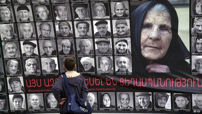 In this photo provided by the Photlure photo agency in Armenia, a boy pauses in front of a wall-sized poster depicting the faces of 90 survivors of the mass killings of Armenians in the Ottoman Empire, in Yerevan, Armenia, April 20, 2005. The composition was done to commemorate the 90th anniversary this Sunday April 24th of the beginning of what Armenians say was the killing of 1.5 million of their people as the Ottoman Turks forced them from eastern Turkey between 1915 and 1923 _ and that this was a deliberate campaign of genocide. (AP Photo/Herbert Bagdasaryan, HO)