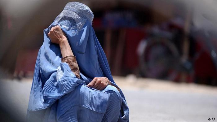 An Afghan woman in veil waits for a bus at a bus stop in Kabul, Afghanistan