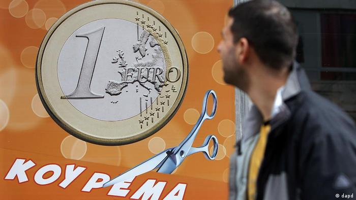 A pedestrian looks at a sign in a shop window: ''One euro, price haircut'' in Athens