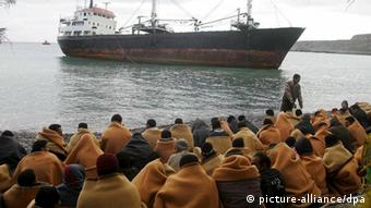 ARCHIV - Rund 200 Flüchtlinge sitzen am Strand von Kato Zacro auf der griechischen Insel Kreta (Archivfotov om 06.12.2007). Sie waren von der Küstenwache von Bord eines kleinen Motorschiffs geholt worden. Menschenrechtler und Europa-Abgeordnete kritisieren seit Monaten unmenschliche Verhältnisse in griechischen Aufnahmelagern. Zudem wurde den Griechen vorgeworfen, mit gefährlichen Manövern wiederholt Flüchtlingsboote zum Kentern gebracht zu haben. Ausserdem untersuche das Land die Anträge von Asylsuchenden nicht gründlich genug und weise Flüchtlinge im Schnellverfahren aus. Foto: Stefanos Rapanis (zu dpa-Korr. Griechenland wächst der Flüchtlingsstrom über den Kopf vom 06.12.2007) +++(c) dpa - Bildfunk++
