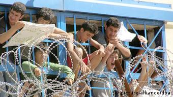 People behind barbed wire at a detention center in Greece in 2009