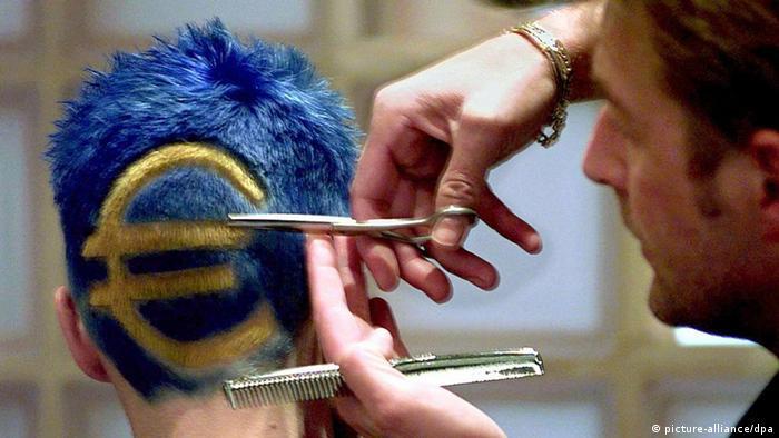 Junger Mann lässt sich gelbes Euro-Zeichen in blaue Haare einfärben. Haare werden geschnitten. dpa (zu dpa 0565 vom 26.01.2012) +++(c) dpa - Bildfunk+++