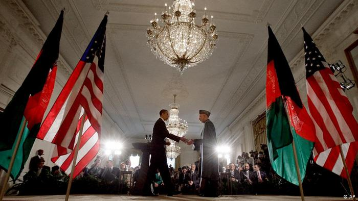 American President Barack Obama walks from the left side of the stage toward Afghan President Hamid Karzai for a handshake.