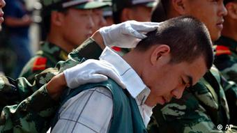 A Chinese paramilitary officer keeps the head of a drug dealer bowed during a public sentencing to mark International Day against Drug Abuse and Illicit Drug Trafficking in Hangzhou, eastern China's Zhejiang province, Monday, June 26, 2006. Chinese drug control officials said Thursday their yearlong war on drugs has severely squeezed heroin supplies from the Golden Triangle. Officials also announced the arrest of some 46,000 drug suspects and the seizure of some 6.9 tons of heroin last year. During the trial in Hangzhou, 20 drug dealers were sentenced today with three given the death penalty and executed soon after. (AP Photo) ** CHINA OUT **