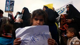 An Iraqi child holding up a sign