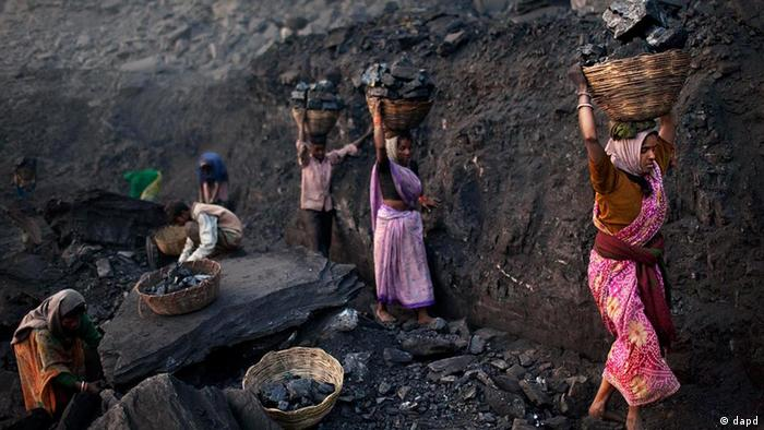 Men and women carrying baskets of coal scavenged illegally at an open-cast mine in the village of Bokapahari in the eastern Indian state of Jharkhand where a community of coal scavengers live and work. (ddp images/AP Photo/Kevin Frayer)
