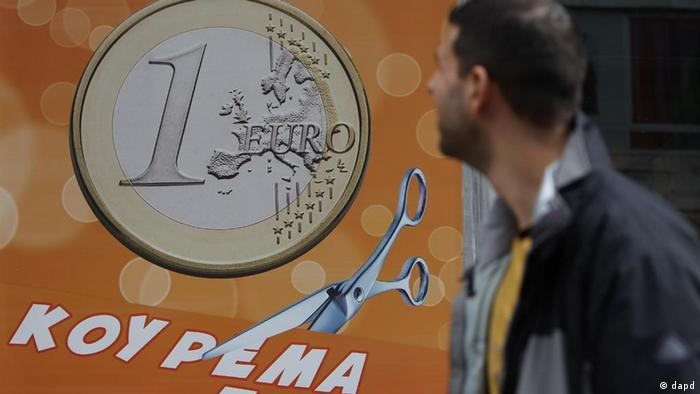 Passer-by looking at Greek euro coin in window