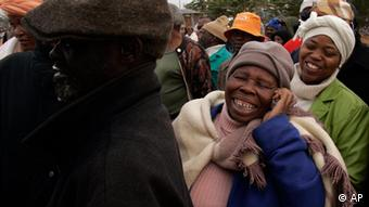 A woman chats on her mobile phone as she queues to cast her vote outside a polling station during 2009 Election in Soweto, South Africa, Wednesday April 22, 2009. (AP Photo/Themba Hadebe)