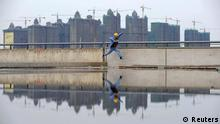 A worker jumps over a puddle near a residential construction site in Taiyuan, Shanxi province in this October 26, 2010 file photo. Global investors worried about a cut to China's official economic growth forecast to 7.5 percent this year would do well to remember the maxim of asset strippers everywhere: the sum of the parts is worth more than the whole. To match Analysis CHINA ECONOMY/GROWTH. REUTERS/Stringer (CHINA - Tags: BUSINESS IMAGES OF THE DAY) CHINA OUT. NO COMMERCIAL OR EDITORIAL SALES IN CHINA